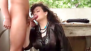 Curly haired brunette milf masturbates on bed and does blow